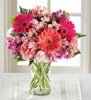 Red pink and purple flower arrangement in a vase