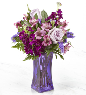 Purple roses and lilies with greens in a purple vase