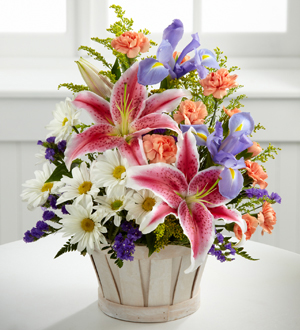 stargazer lilies with irises and daises in a round basket