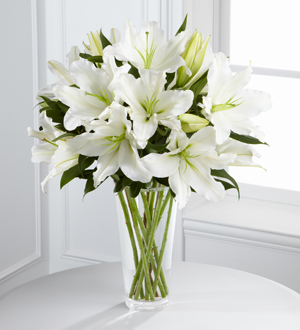 White lilies in a clear vase for funeral